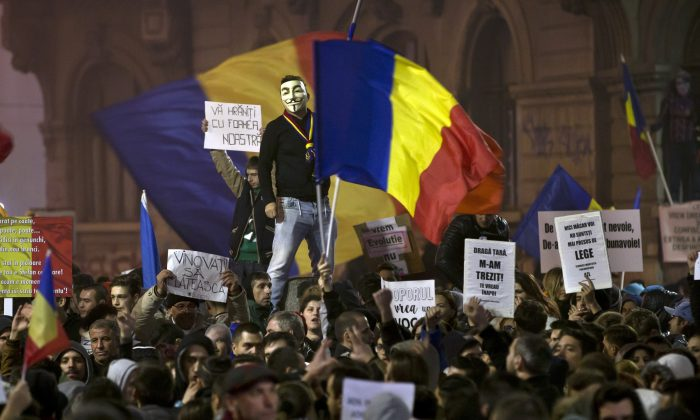 """A man wearing a Guy Fawkes mask stands above protesters shouting slogans against the Romanian politicians during the fourth day of protests, joined by tens of thousands across the country, calling for early elections, in Bucharest, Romania, on Nov. 6, 2015. Large street protests followed the Oct. 30 nightclub fire, which many Romanians blame on a weak enforcement of regulations and corruption. The street protesters have condemned the nation's politicians as arrogant and corrupt and isolated from the problems of ordinary people. Banners read """"You are feeding on our hunger,"""" top left, and """"The culprits must pay,"""" bottom left. (AP Photo/Vadim Ghirda)"""