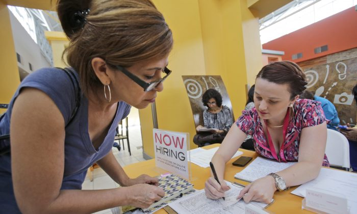 A'GACI clothing store hiring manager Marcie Lowe (R) gives her card to job applicant Xionara Garcia (L) of Miami, during a job fair at Dolphin Mall in Miami on Oct. 6, 2015. (AP Photo/Wilfredo Lee)