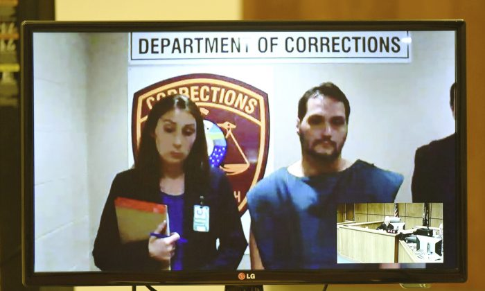 Matthew Dion is arraigned via video on double-murder charges at Manchester District Court in Manchester, N.H., on June 12, 2015. Public Defender Aileen O'Connell is pictured at left. All but one of New Hampshire's district courtrooms are wired for video arraignments of criminal defendants from local jails to enhance security and cut transportation costs. Some defense lawyers object, saying that depicting their clients in a jail setting and jumpsuit taints the presumption of innocence until proven guilty. (David Lane/The Union Leader via AP)