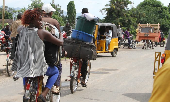 Burundians carry their belongings on bicycles in Bujumbura, Burundi, on Nov. 7, 2015. Holding their prized possessions, scores of people fled Burundi's capital Saturday before a looming security crackdown that has left many predicting more bloody violence ahead. (AP Photo)