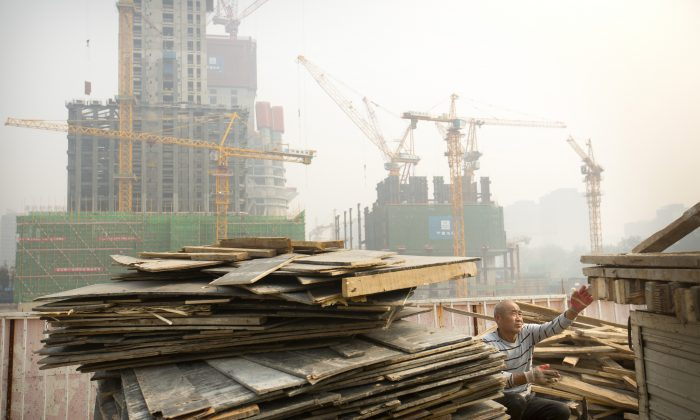 A worker tosses boards onto the back of a truck at a construction site in Beijing on Oct. 6, 2015. (AP Photo/Mark Schiefelbein)
