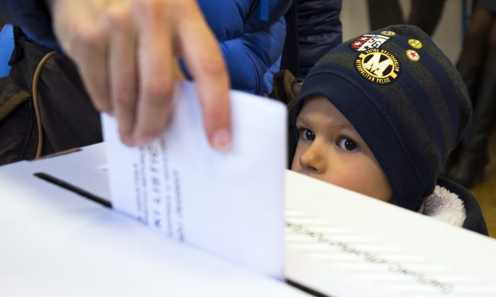 A child looks at a ballot being cast at a polling station in Zagreb, Croatia, Sunday, Nov. 8, 2015. Croatia's ruling center-left coalition faces a strong challenge from a conservative opposition in the Balkan country's first parliamentary election since joining the European Union in 2013. (AP Photo/Darko Bandic)
