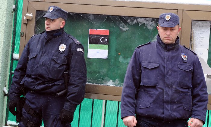 Serbian policemen stand guard in front of the Libyan embassy in Belgrade on Feb. 22, 2011. Some 30 people, mostly Libyans or Serbian citizens of Libyan origin, protested on Feb. 22 in front of the Arab country's embassy against the regime of Muammar al-Qaddafi. The protesters broke the windows of a showcase in front of the embassy, situated in the posh Belgrade area of Dedinje and also tore portraits of Qaddafi, replacing them with an old red-black-green Libyan flag. (Andrej Isakovic/AFP/Getty Images)