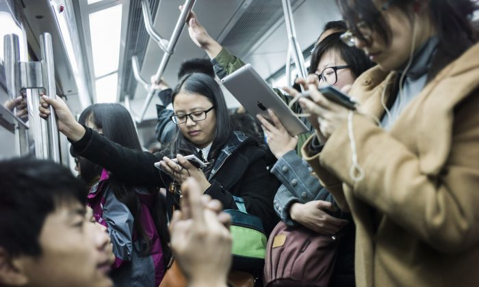 Commuters watch movies on their mobile phones and tablets in a metro car in Beijing, Nov. 17, 2014. (Fred Dufour/AFP/Getty Images)