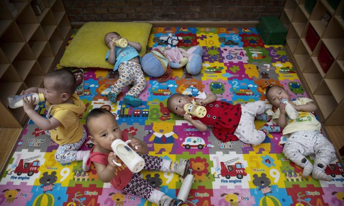 Young orphaned Chinese children drink milk from bottles at a foster care center on April 2, 2014 in Beijing. (Kevin Frayer/Getty Images)