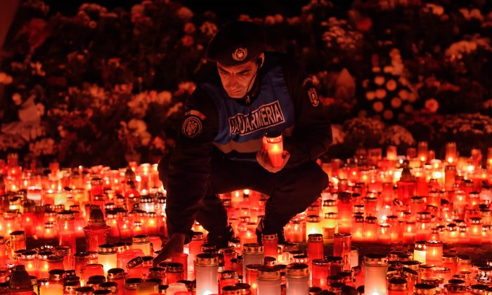 A Romanian gendarme places candles given by the people who came to pay respect for the victims of the fire at the Colectiv nightclub in Bucharest, Nov. 2, 2015. A fire and stampede at the club during the night to Oct. 31, 2015, left at least 39 people dead and nearly 200 injured. (Daniel Mihailescu/AFP/Getty Images)