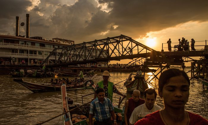 Sun shines in the distance as people ride boats and spend time at the pier on boats and swimming ahead of the landmark Nov. 8 elections, in Yangon, Burma, on Nov. 7, 2015. (Lam Yik Fei/Getty Images)