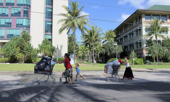 Kionina Kaneso, left, pushes carts of laundry followed by her granddaughter, Keioleen Helly, center, and daughter, Kifency Kinny, past the University of Hawaii John A. Burns School of Medicine near a tent in a homeless encampment in which they lived in Honolulu on Oct. 7, 2015. (AP Photo/Cathy Bussewitz)