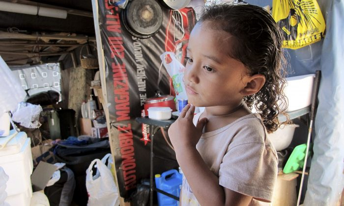 Keioleen Helly, 3, stands inside her family's sidewalk shelter in Honolulu on Oct. 7, 2015. The family was packing up belongings to take to a storage unit two days before the city planned to clear their block of the homeless encampment, hoping to get a ride to the storage unit from a volunteer. (AP Photo/Cathy Bussewitz)