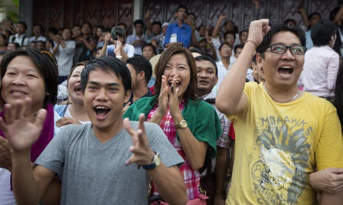 Supporters of Burma's National League for Democracy party cheer as they watch early voting results posted on a giant screen outside the NLD headquarters in Yangon, Burma, Sunday, Nov. 8, 2015. With tremendous excitement and hope, millions of citizens voted Sunday in Burma's historic general election that will test whether the military's long-standing grip on power can be loosened, with opposition leader Aung San Suu Kyi's party expected to secure an easy victory. (AP Photo/Mark Baker)
