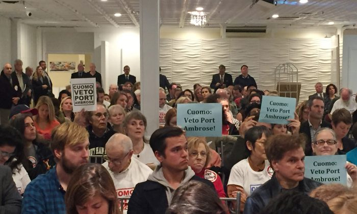 Signs opposing a proposed offshore liquefied natural gas pipeline can be seen in the crowd during a meeting at the Long Beach Hotel in Long Beach, N.Y., on Nov. 2, 2015. Liberty Natural Gas LLC wants to build an offshore gas terminal in the waters between New York and New Jersey that will pump liquefied gas through a subsea pipeline into an existing pipeline running between the two states. (AP Photo/Michael Balsamo)