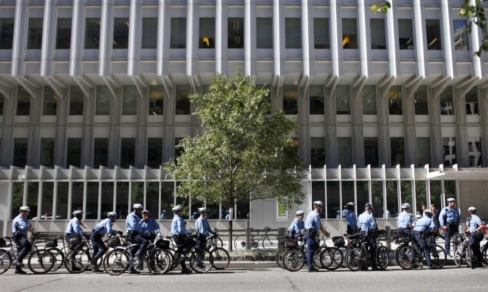 Bicycle police officers line the street outside the World Bank offices in Washington, D.C., during the annual meeting of the World Bank and International Monetary Fund, on Oct. 8, 2010. Climate change could push more than 100 million people into extreme poverty by 2030 by disrupting agriculture and fueling the spread of malaria and other diseases, the World Bank said in a report Sunday Nov. 8, 2015. (AP Photo/Jacquelyn Martin)