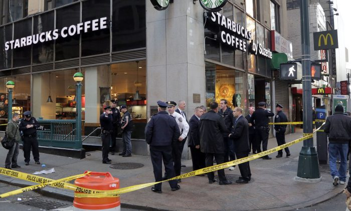 New York Police Department officers investigate a shooting near a subway station entrance at 35th Street and Eighth Avenue, Monday, Nov. 9, 2015, in New York. Authorities said three people have been shot, one fatally. No suspects were immediately arrested. (AP Photo/Mark Lennihan)