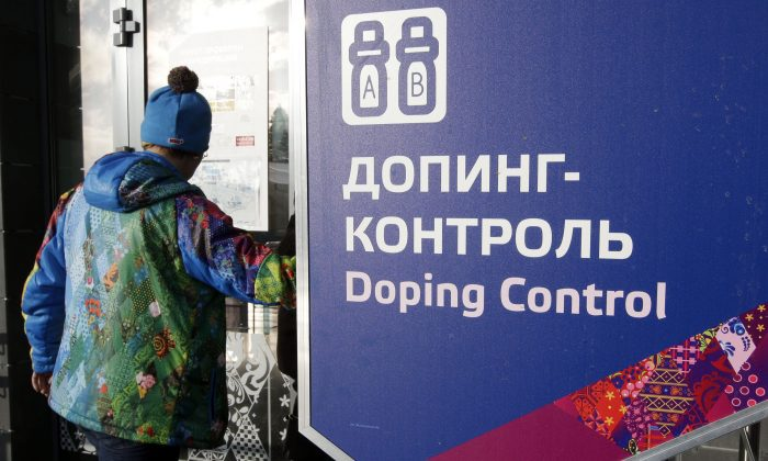 A man walks past a sign reading doping control, at the Laura biathlon and cross-country ski center, at the 2014 Winter Olympics in Krasnaya Polyana, Russia, on Feb. 21, 2014. (AP Photo/Lee Jin-man)