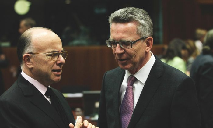 French Interior Minister Bernard Cazeneuve (L) at German Interior Minister Thomas de Maiziere at a meeting of EU justice and interior ministers at the EU Council building in Brussels on Monday, Nov. 9, 2015. EU justice and interior ministers met Monday to discuss the ongoing crisis of migrants and refugees. (AP Photo/Francois Walschaerts)