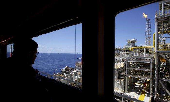 An oil worker looks out, over the Petrobras offshore ship platform over Tupi field in Santos Bay off the coast of Rio de Janeiro, Brazil, on Oct. 28, 2010. (AP Photo/Felipe Dana)
