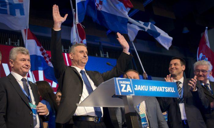 Opposition leader Tomislav Karamarko (2L) celebrates his coalition's winning of majority of votes, in Zagreb, Croatia, early Monday, Nov. 9, 2015. (AP Photo/Darko Bandic)