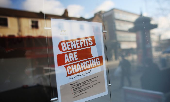 A sign informs members of the public on changes to benefits on Lewisham high street, in London, England, on on Dec. 5, 2012. (Oli Scarff/Getty Images)
