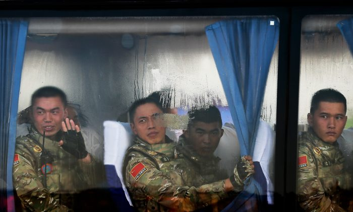 Chinese People's Liberation Army troops look out from a bus as they arrive at Tiananmen Gate in Beijing on Sept. 3. The Chinese regime is planning to restructure its military, and control of its hacker units may be shifted. (Andy Wong/Getty Images)