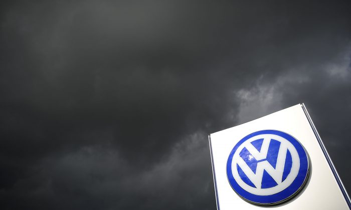 Rain clouds are seen over a Volkswagen symbol at the main entrance gate at Volkswagen production plant in Wolfsburg, Germany, on on Sept. 23, 2015. (Alexander Koerner/Getty Images)