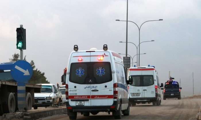 Ambulances leave the King Abdullah bin al-Hussein Training Center where a Jordanian policeman went on a shooting spree in Mwaqar on the outskirts of Amman, Jordan, Monday, Nov. 9, 2015. The policeman opened fire Monday on foreign trainers at a police compound, killing two Americans, a South African and a Jordanian and wounding two Americans and three Jordanians, according to government spokesman Mohammed Momani. (AP Photo/Raad Adayleh)