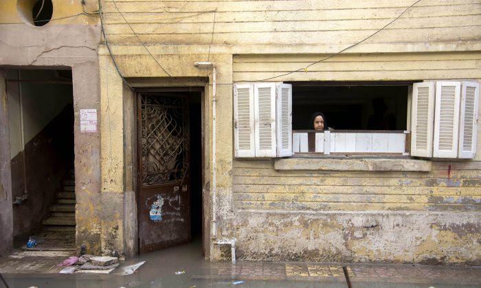A woman looks from her house after a heavy rainfall in the coastal city of Alexandria, Egypt, Sunday, Oct. 25, 2015. (AP Photo/Heba Khamis)