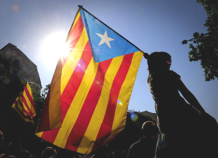 A woman holds the Catalan flag as hundreds of thousands of people marched on July 10 in Barcelona in support of the Catalan region's statute of autonomy. (Josep Lago/Getty Images)