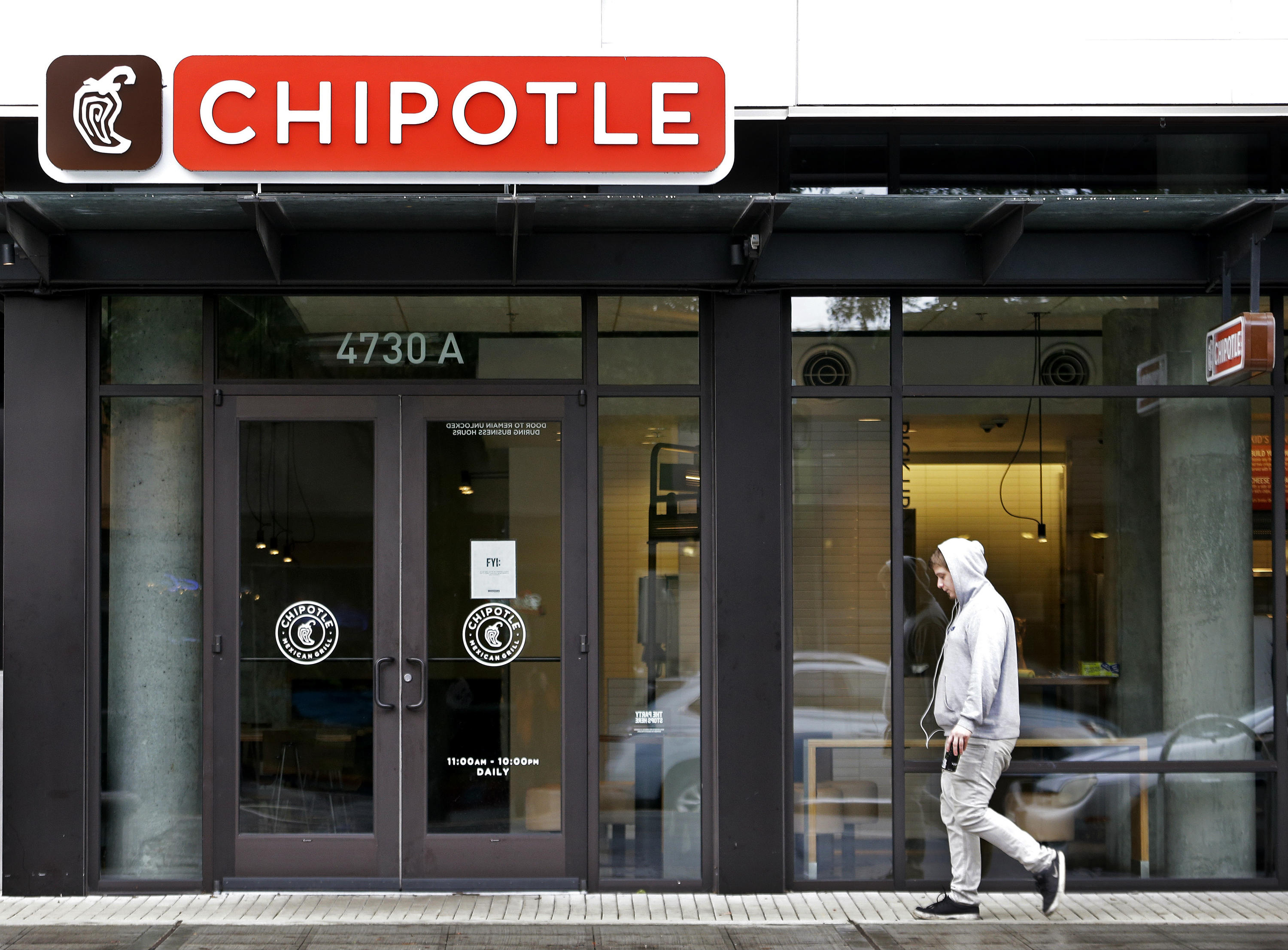 A pedestrian walks past a closed Chipotle restaurant in Seattle on Nov. 2, 2015. Washington state health officials say they have found no source for the E. coli outbreak related to Chipotle and the chain's Pacific Northwest restaurants could reopen later this week. Washington state epidemiologist Dr. Scott Lindquist says all the tests of food from Chipotle stores in Washington and Oregon came back negative for E. coli. (AP Photo/Elaine Thompson)