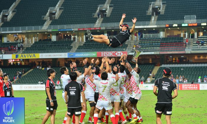 The Japan Rugby Sevens team tosses their coach Tomohiro Segawa into the air in celebration of qualifying for the 2016 Rio Olympics after winning the Asia Rugby Sevens Qualifying competition in Hong Kong on the weekend of Nov 7 – 8, 2015. (Bill Cox/Epoch Times)
