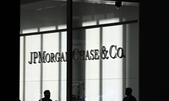 People pass a sign for JPMorgan Chase & Co. at its headquarters in Manhattan on October 2, 2012 in New York City. (Spencer Platt/Getty Images)