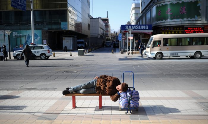 An elderly man rests on a bench in Beijing on Jan. 3, 2014. (Wang Zhao/AFP/Getty Images)