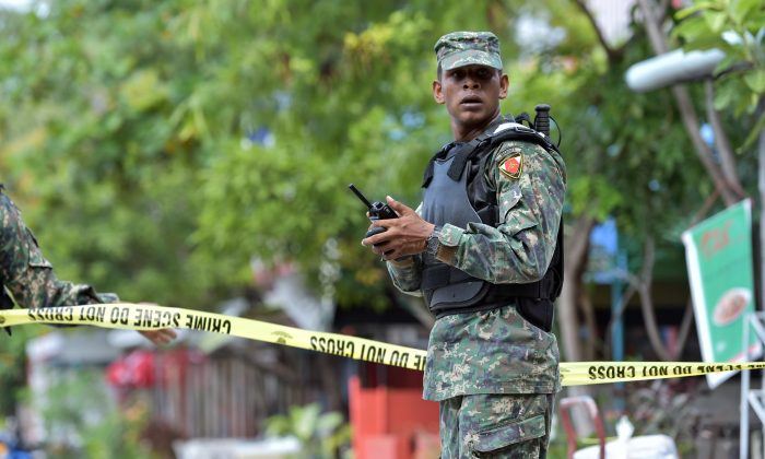 A Maldivian army officer stands guard at a cordoned off area after news of a suspected bomb being found near the harbor area, which turned out to be a false alarm, in Male, Maldives, Thursday, Nov. 5, 2015. (AP Photo/Mohamed Sharuhaan)