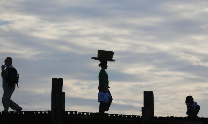 A street vender (C) walks on the historic U Bein Bridge near Amarapura, in Mandalay, Burma, on Nov. 10, 2015. Burma was trapped in a post-election limbo Tuesday with official results barely trickling in, although opposition leader Aung San Suu Kyi's party claimed a victory massive enough to give it the presidency and loosen the military's grip on the country. (AP Photo/Hkun Lat)
