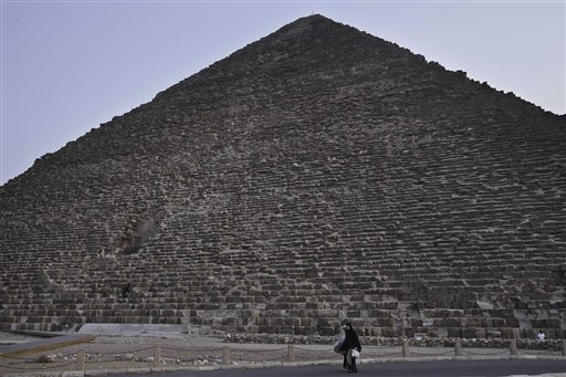 An Egyptian woman walk past the Khufu pyramid in Giza, Egypt, Monday, Nov. 9, 2015. Egypt's Antiquities Ministry says a scanning project in the Giza pyramids has identified thermal anomalies, including one in the largest pyramid, built by Cheops, known locally as Khufu. (AP Photo/Nariman El-Mofty)