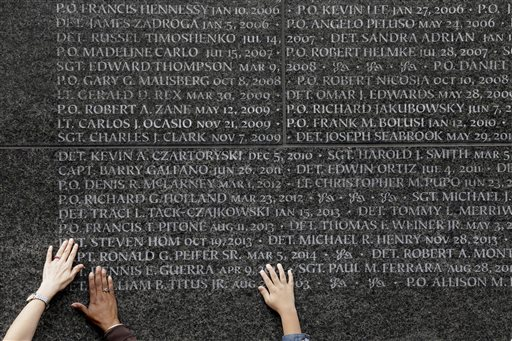 Family members of police officers who died in the line of duty touch the names of their loved ones during a rededication ceremony at the Police Memorial Wall in Battery Park, Tuesday, Oct. 13, 2015, in New York. (AP Photo/Mary Altaffer)