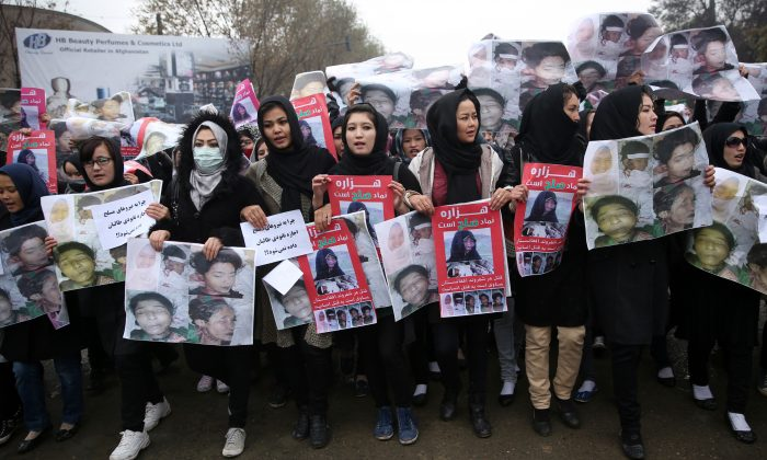 Women march in the Afghan capital of Kabul on Wednesday, Nov. 11, 2015 with pictures showing ethnic Hazaras who were allegedly killed by the Taliban, calling for a new government that can ensure security in the country. Farsi posters carried by the protesters call for security ant call on Preident Ashraf Ghani to resign.(AP Photos/Massoud Hossaini)