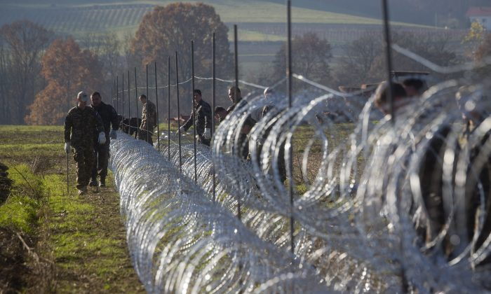Slovenian soldiers erect a razor-wired fence on the Croatian border in Gibina, Slovenia, Wednesday, Nov. 11, 2015. (AP Photo/Darko Bandic)