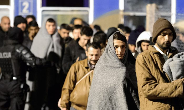 A man wears a blanket as migrants and refugees walk towards a refugee center in Sentilj, after arriving by train on November 4, 2015. (Jure Makovec/AFP/Getty Images)