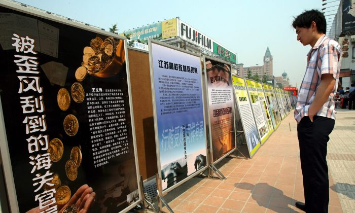 A Chinese man looks at anti-corruption billboards on display in Central Beijing, on June 11, 2007. (Teh Eng Koon/AFP/Getty Images)