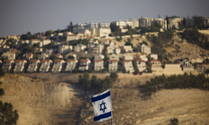 An Israeli flag is seen in front of the West Bank Jewish settlement of Maaleh Adumim on the outskirts of Jerusalem on Sept. 7, 2009. The European Union on Wednesday, Nov. 11, approved guidelines for its member states to specially label products made in West Bank settlements, a move that has already been criticized by Israel. (AP Photo/Bernat Armangue)