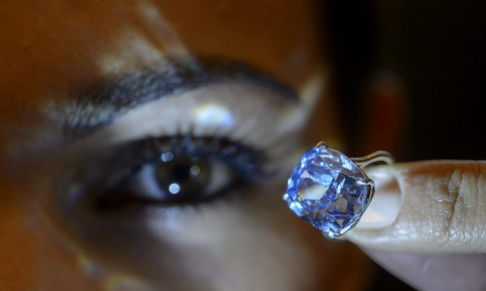 A Sotheby's employee displays the rare Blue Moon Diamond during a preview at Sotheby's, in Geneva, Switzerland, on Nov. 4, 2015. The 12.03 carat blue diamond is the largest cushion shaped fancy vivid blue diamond ever appear at auction. It is estimated to sell between 35 and 55 million U.S. dollars. The auction will take place in Geneva, on Nov. 11, 2015. (Martial Trezzini/Keystone via AP)