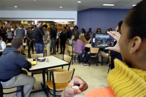 In this Saturday, Nov. 7, 2015, photo, a member of Concerned Student 1950 films a protest in Mark Twain Dining Hall on University of Missouri campus, in Columbia, Mo. (Sarah Bell/Missourian via AP)