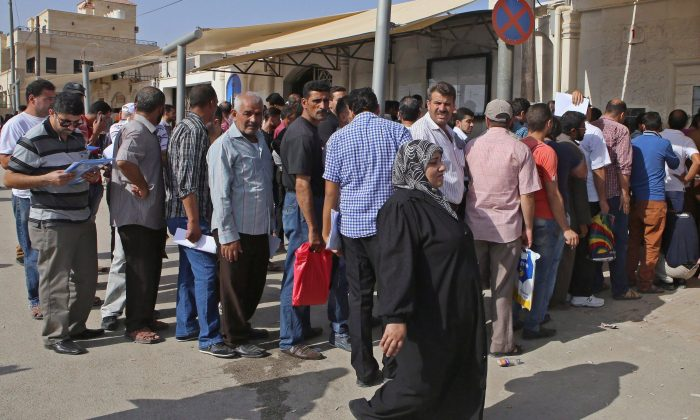 Syrian refugees gather outside their embassy waiting to apply for passports or renew their old passports, in Amman, Jordan, Sept. 15, 2015. (The Canadian Press/ AP/Raad Adayleh)