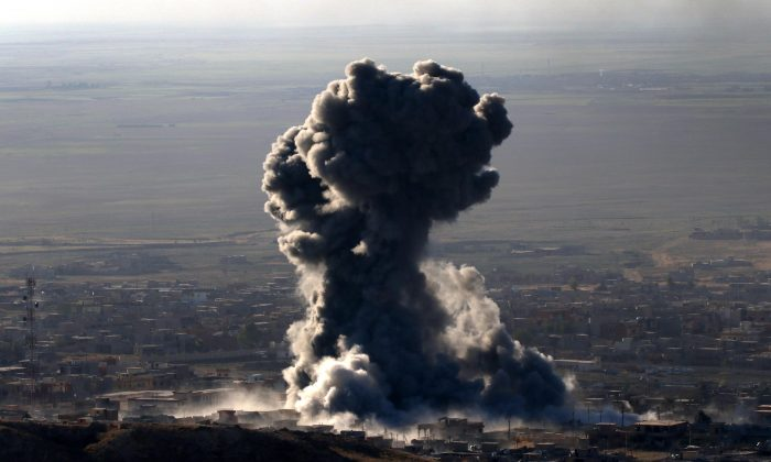 "Heavy smoke billows during an operation by Iraqi Kurdish forces backed by US-led strikes in the northern Iraqi town of Sinjar, Mosul province, on November 12, 2015, to retake the town from the Islamic State group and cut a key supply line to Syria. The autonomous Kurdish region's security council said up to 7,500 Kurdish fighters would take part in the operation, which aims to retake Sinjar ""and establish a significant buffer zone to protect the (town) and its inhabitants from incoming artillery."" AFP PHOTO / SAFIN HAMED        (Photo credit should read SAFIN HAMED/AFP/Getty Images)"