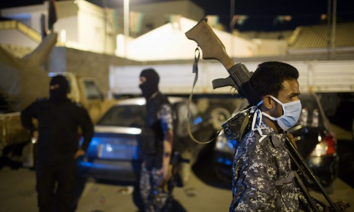 Libyan immigration police gather during a raid on a home holding African migrants on the outskirts of Tripoli, Libya, early Tuesday, Oct. 13, 2015. (AP Photo/Mohamed Ben Khalifa)
