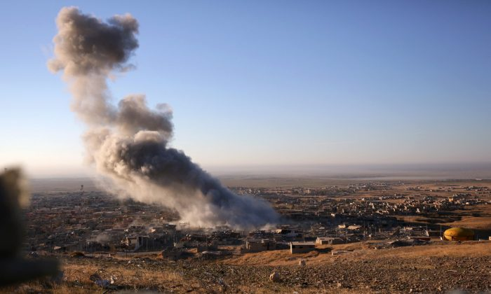 Smoke believed to be from an airstrike billows over the northern Iraqi town of Sinjar on Thursday, Nov. 12, 2015. (AP Photo/Bram Janssen)