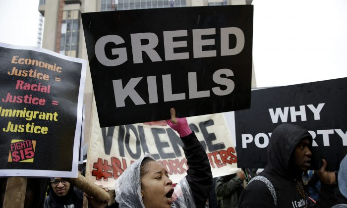 People hold signs and chant slogans during a rally supporting a $15-an-hour minimum wage in New York, Tuesday, Nov. 10, 2015.  (AP Photo/Seth Wenig)