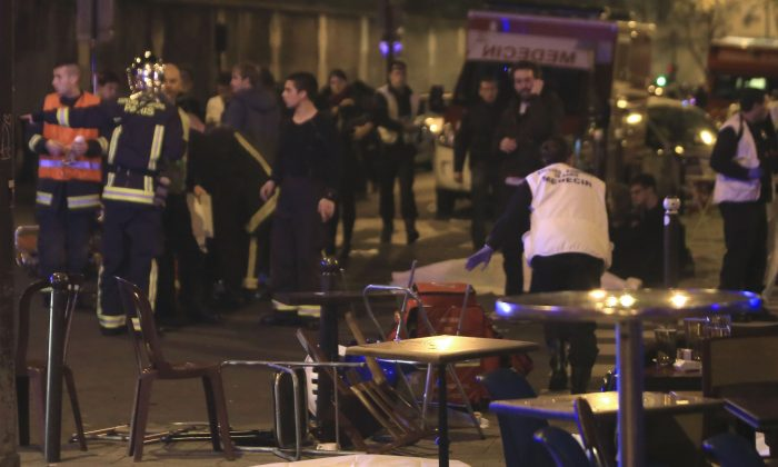 Emergency services attend the scene as victims lay on the pavement outside a Paris restaurant, Friday, Nov. 13, 2015.  Police officials in France on Friday report multiple terror incidents, leaving many dead.  It was unclear at this stage if the events are linked. (AP Photo/Thibault Camus)