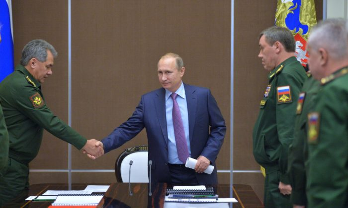 FILE In this Tuesday, Nov. 10, 2015 file photo Russian President Vladimir Putin, centre, shakes hands with Defense Minister Sergei Shoigu at a meeting with defense officials in the Bocharov Ruchei residence in the Black Sea resort of Sochi, Russia. President Vladimir Putin's spokesman said plans for a new submarine-launched nuclear torpedo shown on Kremlin-controlled television were secret and should never have been aired. NTV and Channel One showed a large document — filmed over a military officer's shoulder during a meeting with Putin — with drawings and details of a weapons system called Status-6.  Second right is Chief of the General Staff of the Russian Armed Forces Valery Gerasimov. (Alexei Druzhinin/RIA Novosti, Kremlin Pool Photo via AP)