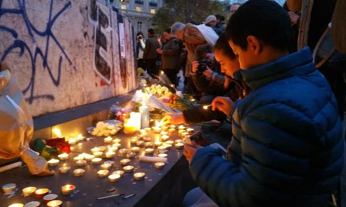 The Monument at the Place de la République in Paris,  became a gathering point for people honoring the victims of the deadly terrorist attacks that tore through Paris the previous night, on Nov. 14, 2015. (David Vives/Epoch Times)